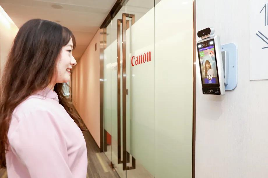 Funcionário deve sorrir para a câmera, para liberar a porta da sala, no escritório. Foto: Canon Information Technologies.
